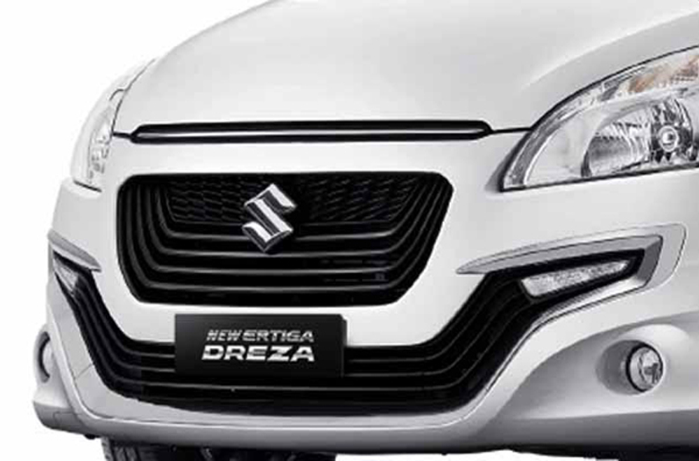 Suzuki Ertiga ได้รับการตกแต่งภายนอกอย่างประณีตด้วยไฟหน้าแบบโปรเจคเตอร์ กระจังหน้าสีดำเงาดีไซน์ใหม่ล่าสุด กันชนหน้าแบบสปอร์ต และ สเกิร์ตข้าง ติดตั้งไฟตัดหมอกคู่หน้าแบบ Front For Lamps ตกแต่งด้วยกรอบโครเมียม